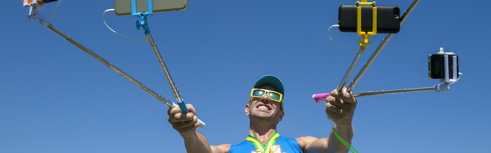 Man holding multiple selfie sticks