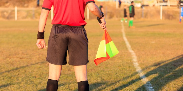 Image of linesman holding flag at soccer
